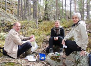 SYS-kulttuuristipendiaatti Nathalie Zwimpfer sekä paikallisosaston Ruth Kostiainen ja Kari Piskonen lepotauolla Astuvansalmen kalliomaalauksilta palattaessa 2012.